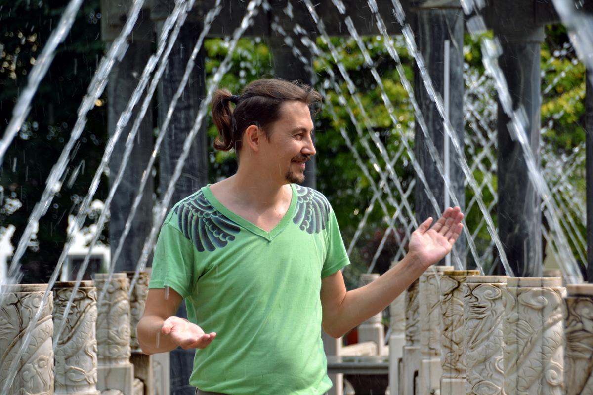 7. Артём плещется в струях фонтана.